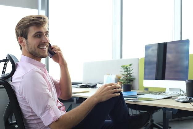 Moderne zakenman praten aan de telefoon terwijl hij op kantoor zit.