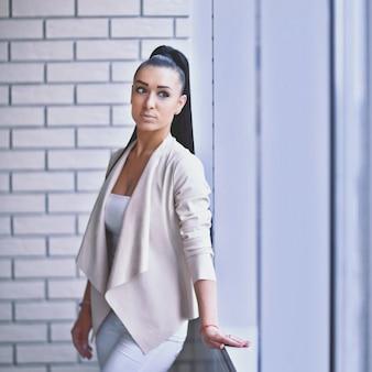 Moderne zakenvrouw die bij het raam in de gang staat