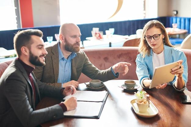 Moderne zakenvrouw in glazen aan tafel zitten en informatie op tablet tonen aan collega's terwijl ze de inhoud van het contract bespreken