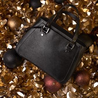Moderne zwarte lederen tas voor een zakelijke vrouw onder kerstversiering.