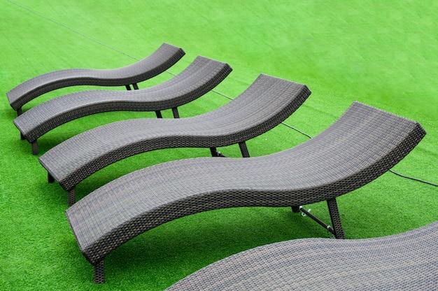 Moderne zwarte ligstoelen op kunstgras op zwembad