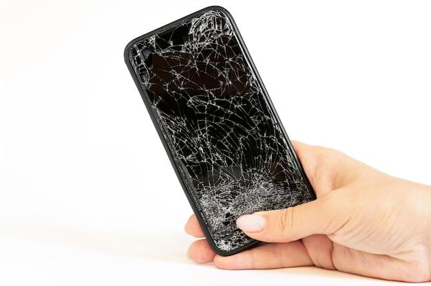 Moderne zwarte smartphone met sterk gebroken scherm in vrouwenhand op witte muur