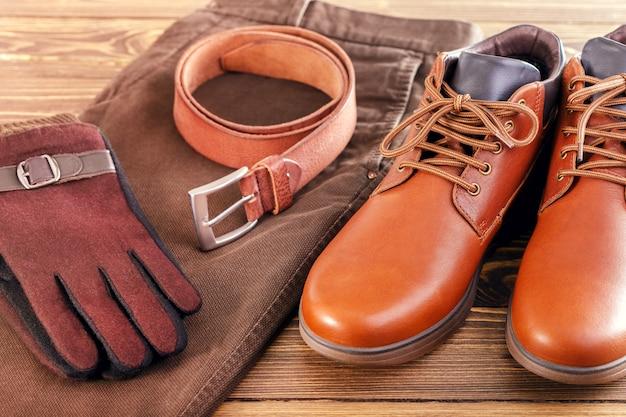 Modetrend voor heren-jeans, lederen schoenen, lederen riem, handschoenen op houten oppervlak.