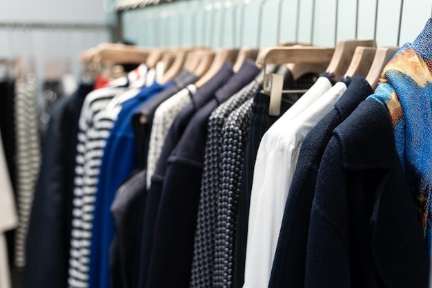 Modetrendconcept. warme winter dameskleding collectie met gebreide wollen truien op houten hangers.