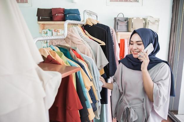 Modewinkel klant praat aan de telefoon tijdens het winkelen