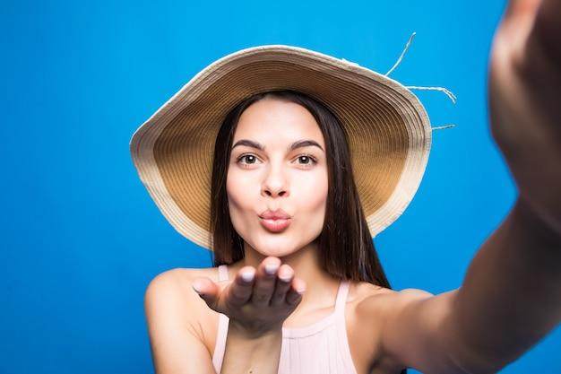 Modieus aantrekkelijk meisje in zonnebril en strooien hoed stuurt luchtkus naar camera. leuke speelse en gelukkige vrouw met rode lippen op blauwe muur. met kopie ruimte.