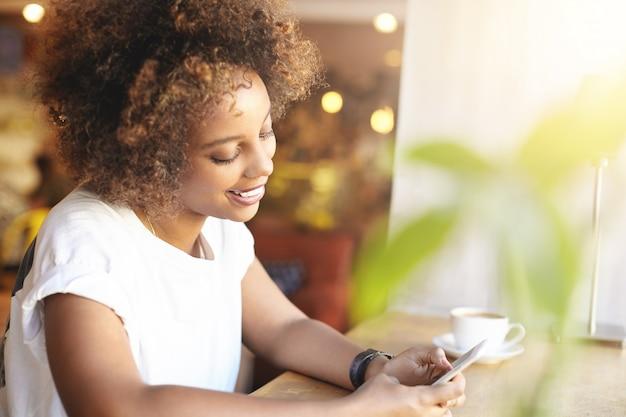 Modieus afrikaans student meisje met stijlvol krullend haar met behulp van high-speed internetverbinding, nieuwsfeed controleren, berichten leuk vinden met een vrolijke glimlach, cappuccino hebben, ontspannen in café na college