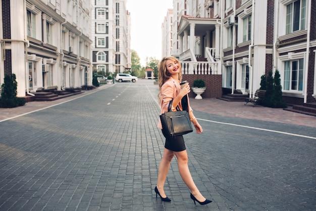 Modieus blond meisje met lang haar, wandelen in zwarte jurk rond britse wijk. ze houdt koffie vast
