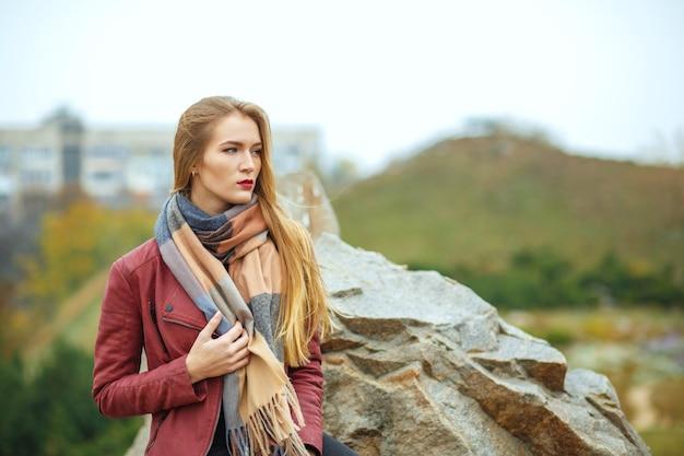 Modieus blond meisje met sjaal en jas, die zich voordeed in de botanische tuin in de buurt van de rotsen. ruimte voor tekst