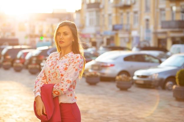 Modieus brunette model dat een blouse draagt en een jas vasthoudt die poseert met zacht avondlicht. ruimte voor tekst
