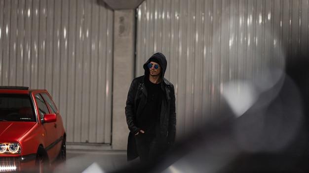 Modieus brutaal manmodel met capuchon met zonnebril in een stijlvol zwart leren jack met een hoodie loopt 's nachts op de parkeerplaats