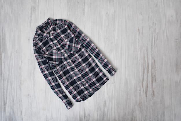 Modieus concept. geruit overhemd op een houten achtergrond. vrouwelijke garderobe