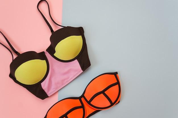 Modieus concept. heldere bovenkant en lijfje van het zwempak, zachte roze en blauwe achtergrond. plaats voor tekst