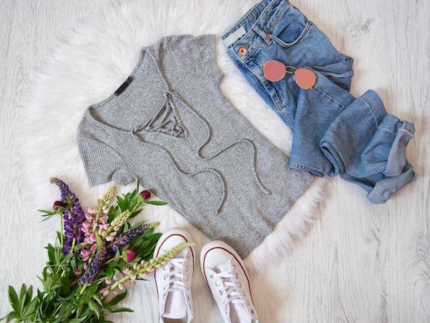 Modieus concept. street style. grijs shirt met veter, jeans, sneakers en boeketten met bloemen.