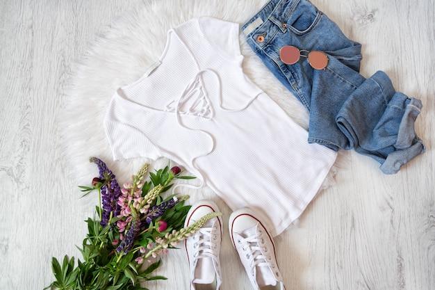 Modieus concept. street style. wit t-shirt met veter, jeans, gympen en boeketten met bloemen.