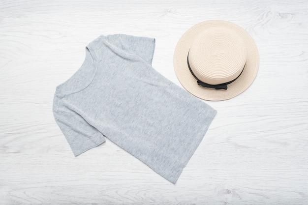 Modieus concept. vrouwelijke zomergarderobe. strohoed en grijs t-shirt. bovenaanzicht