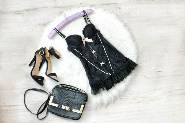 Modieus concept. zwart kanten ondergoed, handtas en schoenen op de witte vacht.