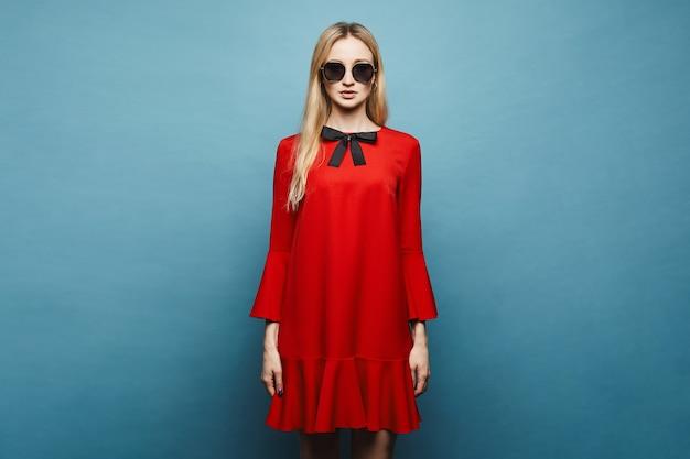 Modieus en glamoureus blond model meisje in stijlvolle zonnebril en in glamoureuze korte rode jurk met zwarte strik poseren