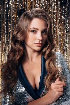 Modieus en luxueus brunette in een moederbord met pailletten en gezond sterk haar kwam naar het nieuwjaarsfeest