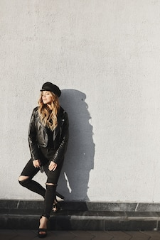 Modieus en sensueel blond model meisje in een zwart leren jas, in zwarte trendy jeans en in stijlvolle hoed glimlachend en poseren met gesloten ogen buitenshuis