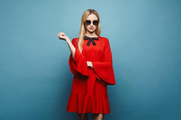 Modieus en sexy blonde model meisje in stijlvolle zonnebril en in glamoureuze korte rode jurk met zwarte strik poseren, geïsoleerd