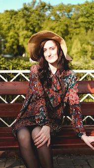 Modieus geklede jonge mooie vrouw op straat op een zonnige dag. mooi meisje in jurk en hoed zit op een bankje en lacht. street-fashion concept