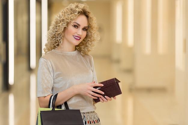 Modieus geklede vrouw met boodschappentassen in winkelcentrum. jong stijlvol meisje met portemonnee. winkelconcept