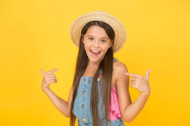 Modieus gekleed meisje. genieten van vakantie. goed gevoel. strand stijl. schoonheid in hoed. portret van gelukkig vrolijk meisje in zomer hoed gele achtergrond. chique outfit. zomer mode. zomervakantie.