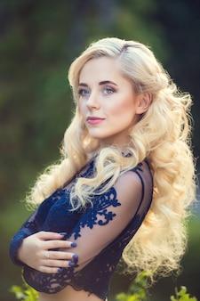 Modieus haar slordige vlecht rond het hoofd. gelukkig mooi jong model meisje in zomer bloesem park.