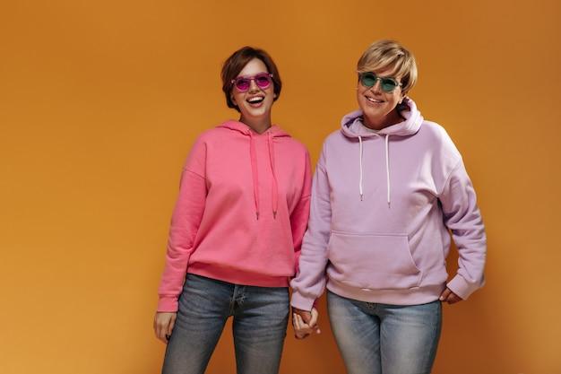 Modieus jong donkerbruin meisje in roze zonnebril en hoodie lachen en hand te houden oude dame in groene glazen op oranje achtergrond.