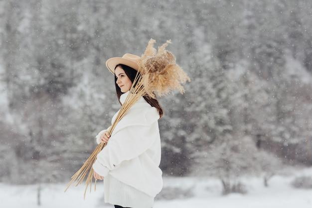 Modieus jong meisje in trendy witte winterkleren en hoed vormt met boeket van riet in besneeuwde winterlandschap bij sneeuwval.