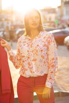 Modieus jong model in kostuum en blouse poseren met zacht avondzonlicht