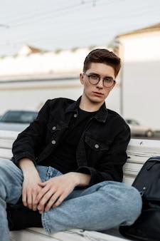 Modieus jonge man model met kapsel in stijlvolle denim casual kleding in stijlvolle bril met zwart lederen rugzak ontspant op houten bankje buiten. knappe moderne man rust bij zonsondergang.