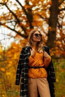 Modieus kaukasisch schoonheidsmeisje met stijlvolle bril in herfstmodekleding met jas en trui buitenshuis
