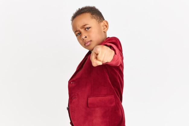Modieus kind met rode blazer die naar voren wijst