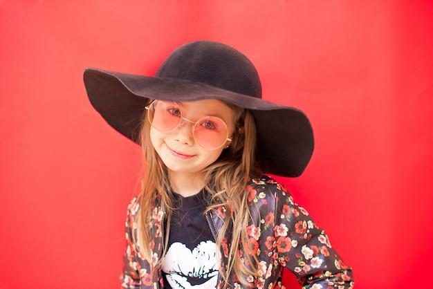 Modieus kindmeisje in grote zwarte hoed op rode muur