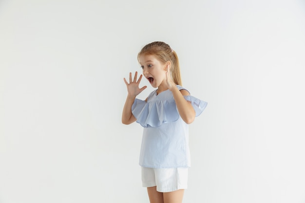 Modieus klein glimlachend meisje poseren in vrijetijdskleding geïsoleerd. kaukasisch blond vrouwelijk model. menselijke emoties, gezichtsuitdrukking, jeugd. geschokt, verbaasd.