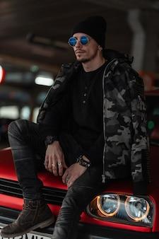 Modieus knap man-model met stijlvolle zonnebril en een zwarte hoed in een militaire winterjas zit op een rode auto in de stad