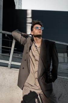 Modieus knappe jongeman model met zonnebril in stijlvol grijs pak met jas en shirt in de stad bij zonlicht. mannelijke stedelijke zakelijke stijl en succes