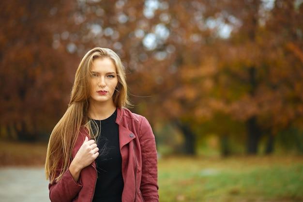 Modieus langharig blond meisje met een jas, die zich voordeed in de botanische tuin. ruimte voor tekst