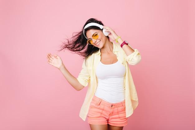 Modieus latijns-meisje in goed humeur poseren voor foto en dansen. enthousiaste spaanse jonge dame in zomer outfit ontspannen terwijl het luisteren naar favoriete liedje.