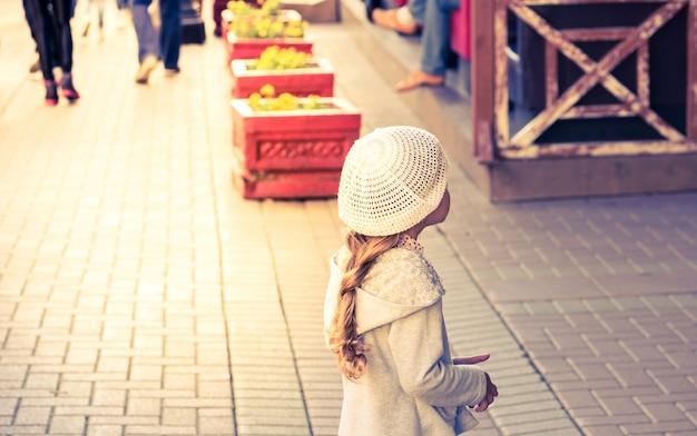 Modieus lief klein meisje met lang haar in een lichtgrijs jasje en een witte breihoed die raam winkelen op arbat-straat in vintage toon en warm licht toevoegt, moskou, rusland