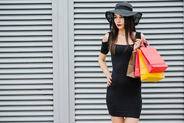 Modieus meisje bedrijf boodschappentassen staan