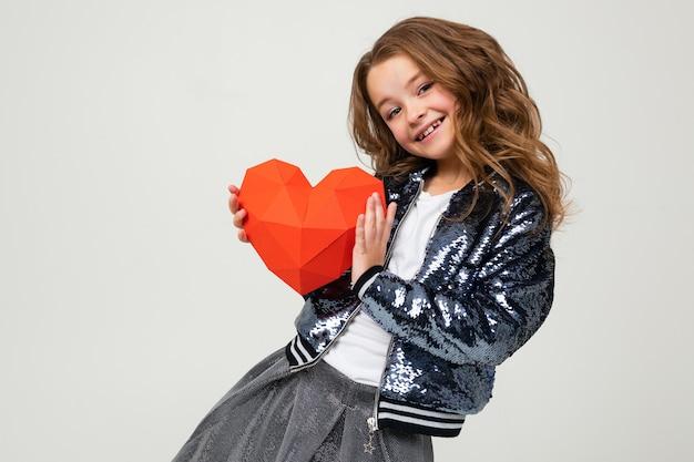 Modieus meisje dat een document hart op een witte muur houdt