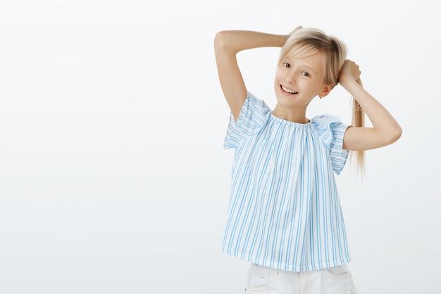 Modieus meisje dat haar eerste oorringen toont aan vriend. portret van een gelukkig speels europees kind, blond haar in handen houden, vlechten maken en breed glimlachend, voor de gek houden over grijze muur
