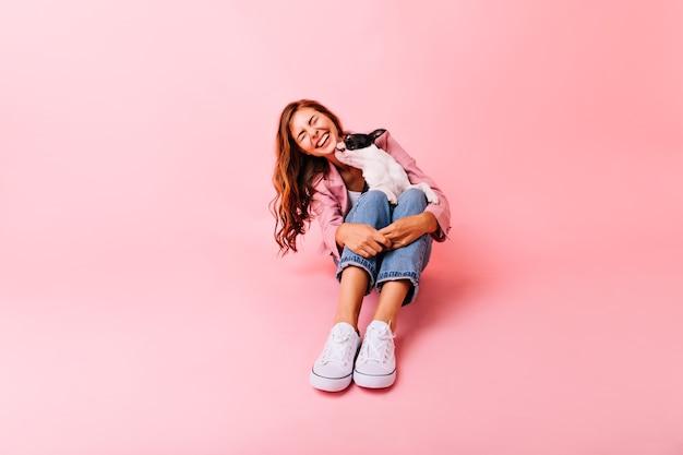 Modieus meisje dat in witte schoenen met hond speelt. spectaculair vrouwelijk model poseren met puppy op haar knieën en lachen.