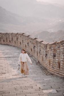Modieus meisje die de grote muur van china bezoeken dichtbij peking tijdens de herfst