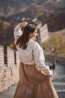Modieus meisje die de grote muur van china bezoeken dichtbij peking tijdens de herfstseizoen.
