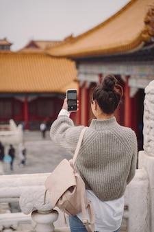 Modieus meisje die de verboden stad in peking china bezoeken