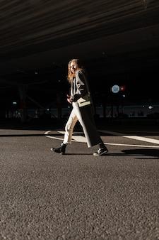 Modieus meisje in een modieuze herfstjas en laarzen met een tas loopt door de stad in het zonlicht